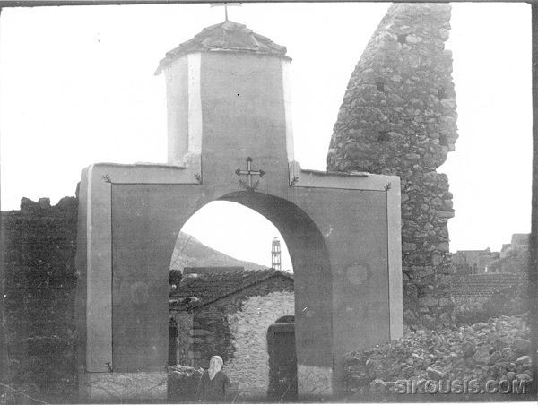 "The old entrance to the Agios Georgios Monastery ""Stavros"". In the background the Agios Panteleimon bell tower can be seen as well as part of the monastery exterior wall that was destroyed during the 1881 earthquake. A 1928 picture by Perikles Papahatzidakis.<br>From the Archives of Vaggelis Roufakis."